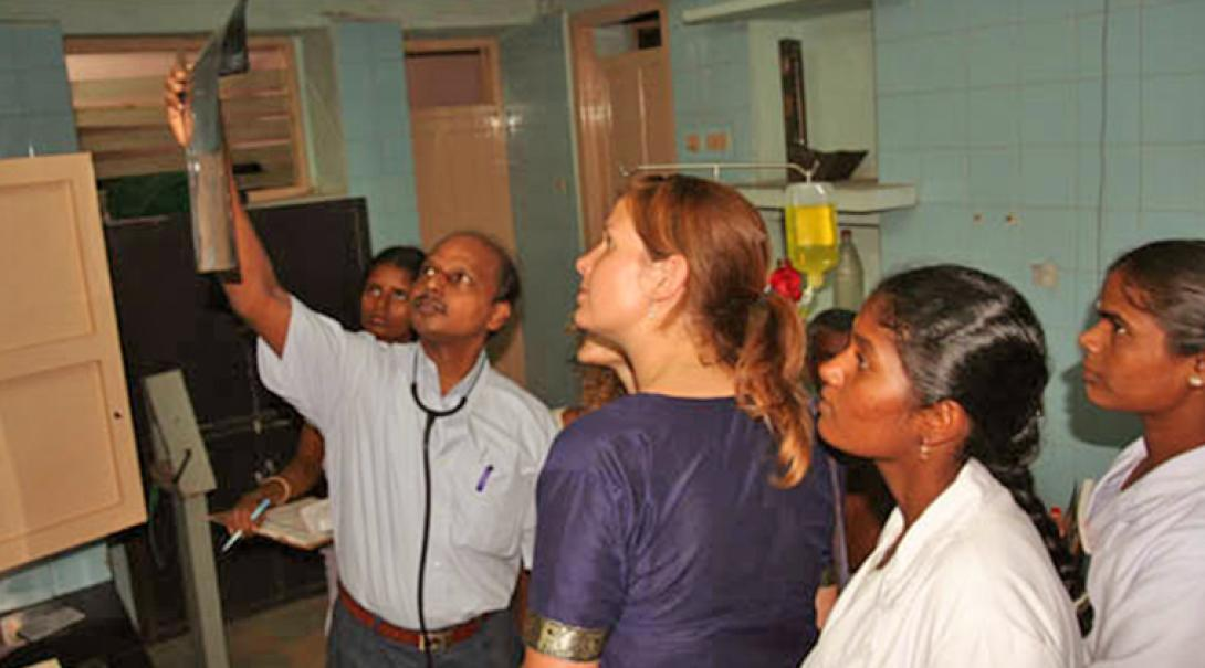 Nursing interns listen to a doctor as he describes the injuries and treatment of a patient in India.